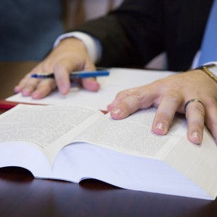 Hands over a legal book represents the hands-on approach at Martin & Tune